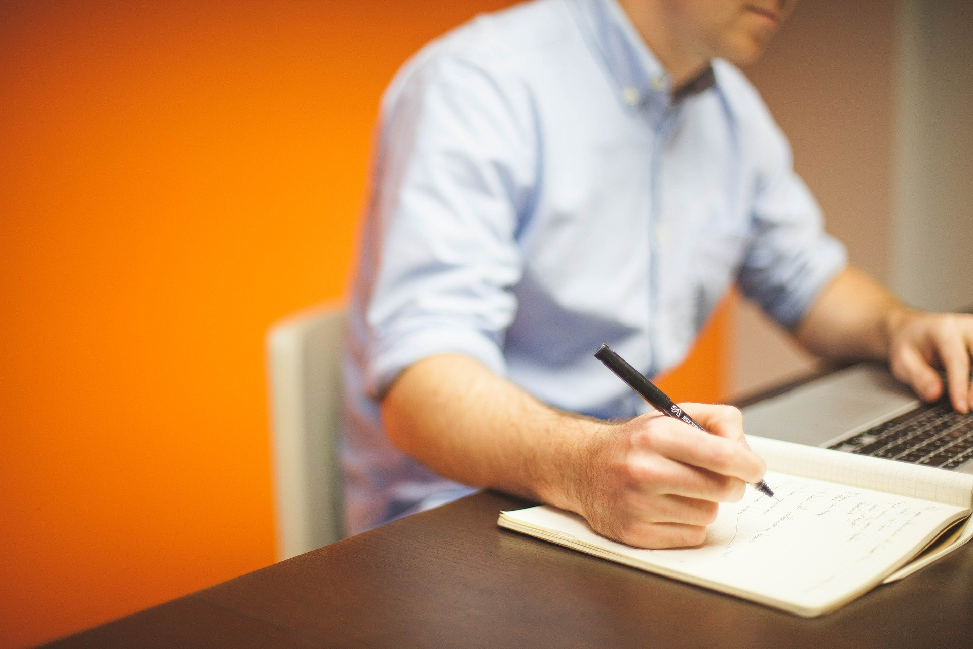 A worker working at a desk with a pad and pen.